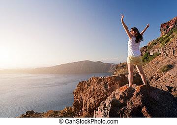 gelukkige vrouw, op, de, rots, met, handen, boven., santorini eiland, griekenland