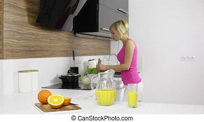 gelukkige vrouw, slaatje, dancing, groentes, moderne, keuken, sap, muziek, het koken, sinaasappel, thuis, meisje, luisteren, drinkt, glimlachen, vermenging