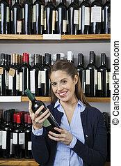 gelukkige vrouw, vasthouden, wijn fles, in, supermarkt