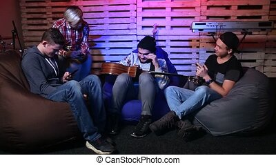 Generation Z musicians sitting on bean bag chairs on the stage using their mobile phones and chatting against musical instruments background. Music band relaxing after practice and training.