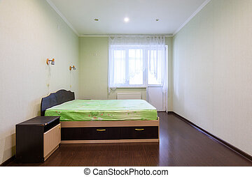 General view of an empty bedroom in a one-room apartment