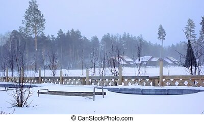 general view of the ski resort in Siberia In a blizzard. Wooden houses at forest and christmas tree