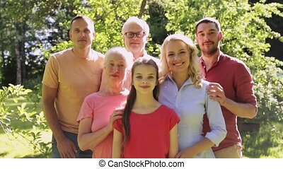 happy family showing thumbs up in summer garden -...