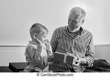 generation. grandfather and grandson with gift box sitting ...