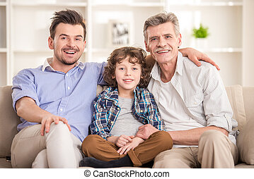 Generation portrait. Grandfather, father and son sitting on...
