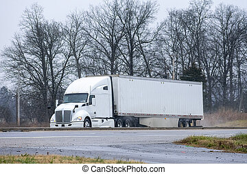Generic White Tractor Trailer Drives In Mixed Rain and Snow