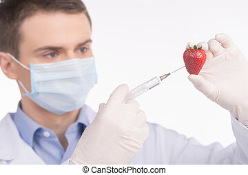 Genetic food engineering concept with fresh red strawberry. man holding strawberry and giving injection