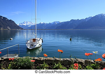 White sailing boat on Geneva lake at Montreux in front of Alps mountain by spring day, Switzerland