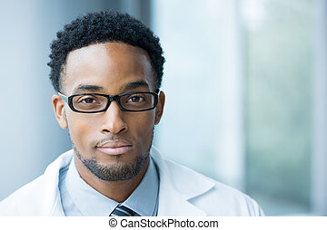 Closeup portrait head shot of friendly, smiling confident male doctor, healthcare professional with a white coat, black glasses, isolated hospital clinic background.