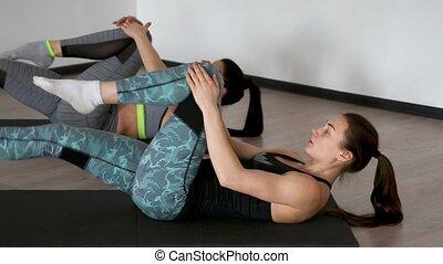 genoux, pilates, nattes, gymnase, étirage, filles, deux, dos, thighs., leur, poitrine, muscles, traction, exercice, pendant, mensonge