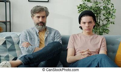 gens, fils, séance, portrait, regarder, divan, papa, armes traversés, appareil photo, malheureux
