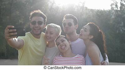 gens, prendre, selfie, photo, grimacer, dehors, dans parc, jeune, amis, groupe, poser, lumière naturelle