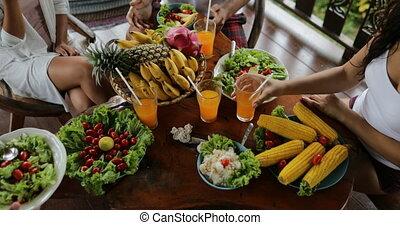 gens, tintement, jus, lunettes, table, à, plats, de, fruits tropicaux, et, salade, sommet, angle, vue, amis, manger, sain, nourriture végétarienne