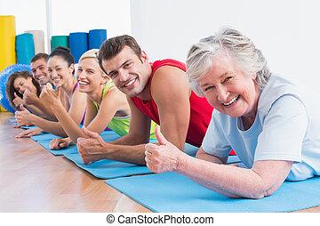 gente, el gesticular, pulgares arriba, mientras, acostado, en, esteras, en, gimnasio