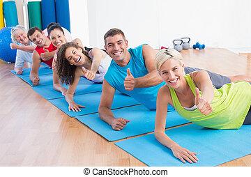 gente, en, felpudos de ejercicio, el gesticular, pulgares arriba, en, gimnasio