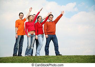 gente, en la hierba, con, el, manos levantadas
