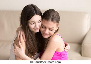 gentilmente, divano, giovane, due, abbracciare, amici, donne