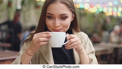 Gentle female drinking coffee - Young and pretty female in...