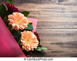 Gentle flowers on wooden background, top view. Bouquet for congratulations, wedding flowers closeup. Decoration made of chrysanthemums, daisies, green plants for birthday card. Selective soft focus.