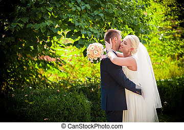 gentle kiss the bride and groom on nature