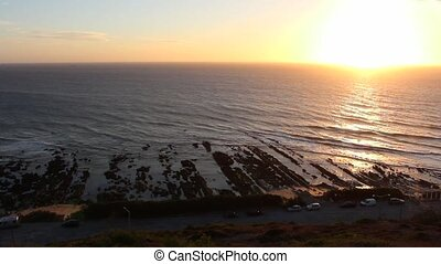 Gentle Ocean waves on rocky shore during the sunset, seen from a viewpoint in Cabo Mondego, in Portugal.