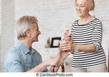 Gentle patient woman helping her husband