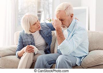 Gentle senior woman consoling her beloved husband