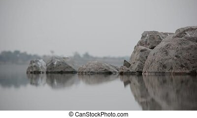 Gentle water Flowing on rocks with rock reflection
