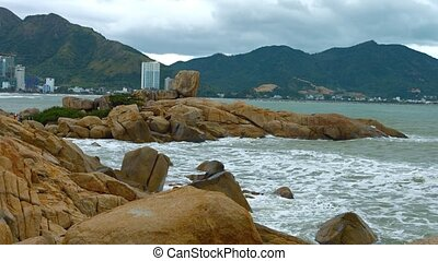 Gentle waves and sea foam splash against the Hon Chong Rocks on a cloudy day in Nha Trang, Vietnam. Video 4k