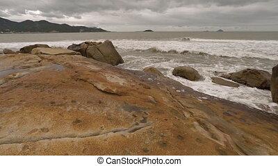 Gentle waves wash the enormous boulders of Hon Chong Rocks near Nha Trang, Vietnam, under an overcast sky.