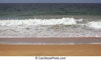 Gentle waves break over the Sand at a Hikkaduwa Beach