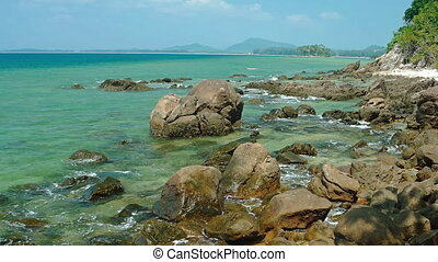 Gentle Waves Lap against Boulders on a Tropical Beach