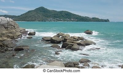 Gentle Waves Splash over a Rocky Tropical Beach