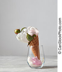 Gentle white flower, bud and green leaf with petals in glass vase on gray stone table.