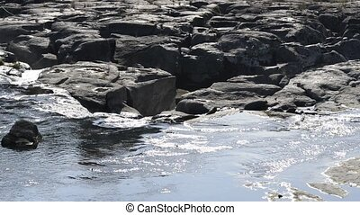Gentle wide river flowing over the rock mass which fails of...
