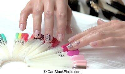 Gentle woman hands choosing color. Well-groomed hands of...