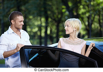 A young man helps a girl get in the car