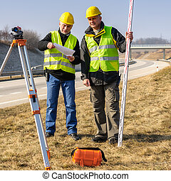 Geodesist two man theodolite stand highway - Two male ...