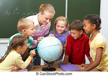 Geography lesson - Portrait of pupils looking at globe while...