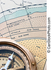 A surveying compass resting on a detailed geological map.