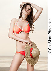 Georgian girl on the beach with a straw hat - a beautiful...