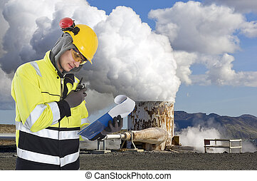 Geothermal engineer and geologist reading data from a list at a gothermal power plant in Iceland, creating hot water and sustainable energy from natural resources