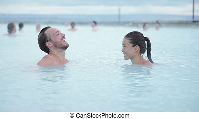 Geothermal spa. Young couple relaxing in hot spring pool in Iceland. people enjoying bathing in a blue water lagoon Icelandic tourist attraction,