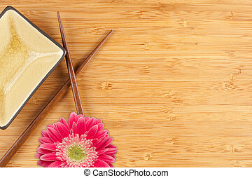 Gerber Daisy, Chopsticks and Dish on a Bamboo Background