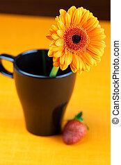 gerbera flower in a black cup of the orange fabric