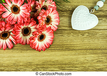 Gerbera flowers with a white heart on a rustic wooden background