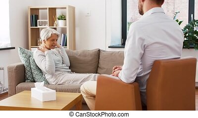 senior woman patient talking to man psychologist - geriatric...