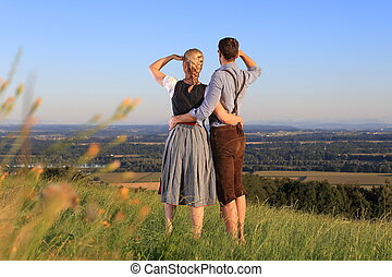 German Couple in Bavarian Costume on the lookout in nature -...