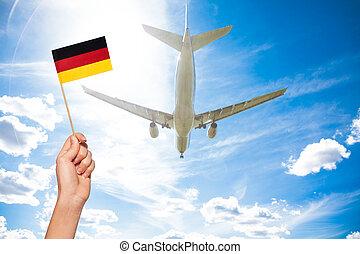 German flag against airplane flying through sky