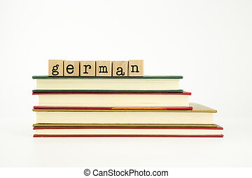 german word on wood stamps stack on books, foreign language and translation concept